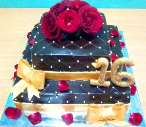 Dark ganache base mediumwith red roses and touch of gold fondant ribbon